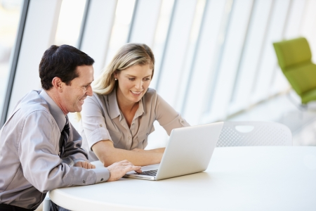 dos personas conversando: Los empresarios tener la reuni�n alrededor de la mesa en la oficina moderna