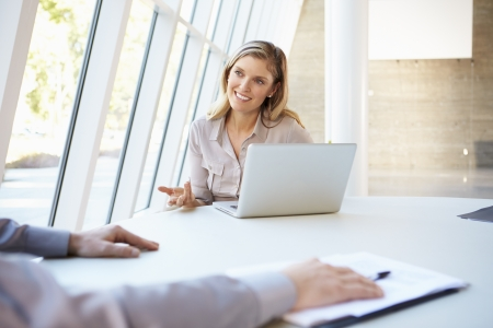 two people talking: Business people Having Meeting Around Table In Modern Office Stock Photo