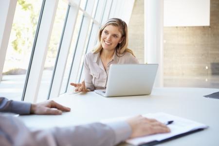 dos personas hablando: Los empresarios tener la reunión alrededor de la mesa en la oficina moderna