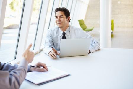 dos personas conversando: Dos hombres de negocios tener la reuni�n alrededor de la mesa en la oficina moderna