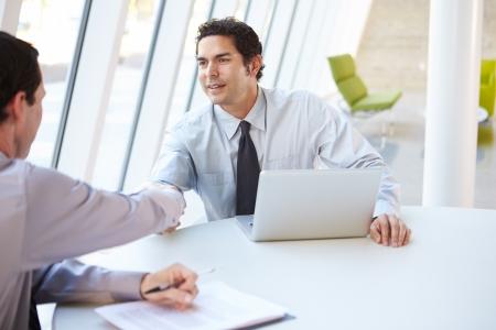 dandose la mano: Dos hombres de negocios tener la reuni�n alrededor de la mesa en la oficina moderna