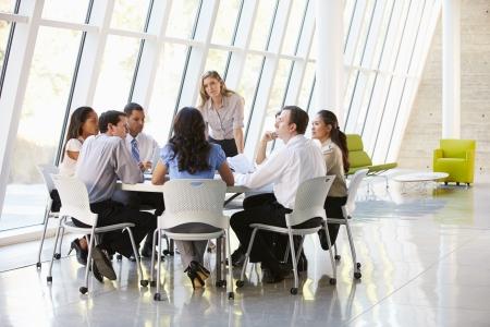 Zakenmensen hebben van Board Meeting In Moderne Kantoor