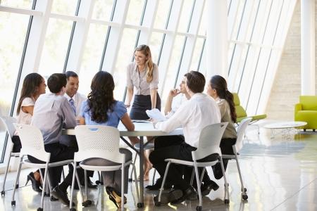 近代的なオフィスに理事会を持つビジネス人々
