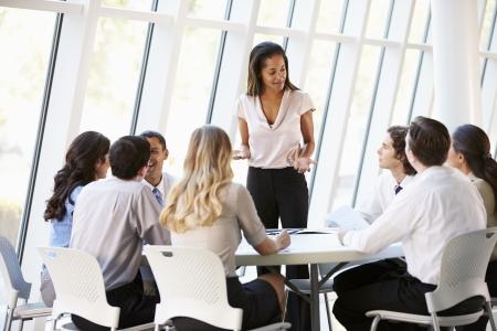 afroamericanas: Las personas de negocios que tienen reuni�n de la Junta en la oficina moderna