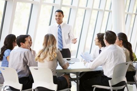 negócio: Executivos que têm Reunião do Conselho no escritório moderno
