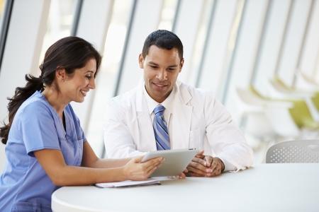 personal medico: Doctor Y Enfermera Tener reunión informal en el comedor del Hospital