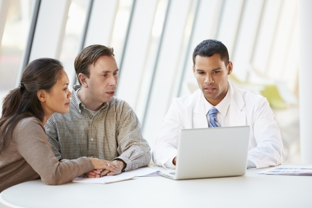 concerned: Doctor Using Laptop Discussing Treatment With Patients Stock Photo