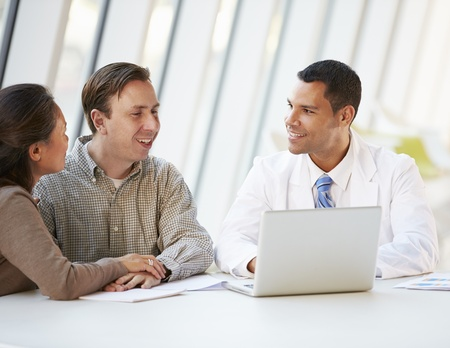 asian medical: Doctor Using Laptop Discussing Treatment With Patients Stock Photo