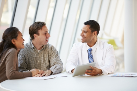 medico con paciente: Doctora Usar el ordenador Tablet hablar sobre el tratamiento del paciente de