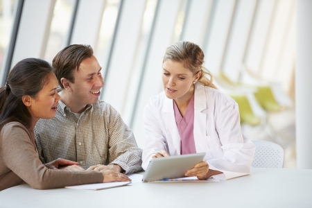 couple talking: Female Doctor Using Digital Tablet Talking With Patients