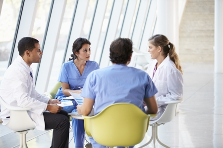 staff meeting: Medical Team Meeting Around Table In Modern Hospital