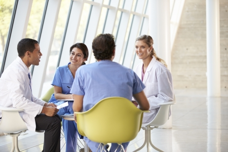 Medical Team Meeting Around Table In Modern Hospital