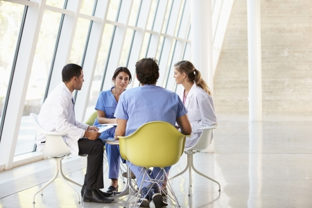 modern hospital: Medical Team Meeting Around Table In Modern Hospital