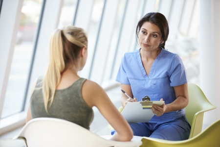 Nurse Meeting With Teenage Girl In Modern Hospital photo