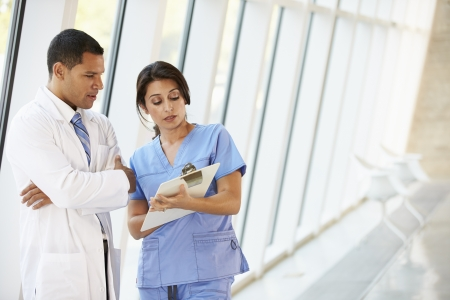 Medical Staff Having Discussion In Modern Hospital Corridor photo