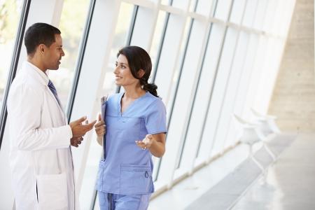 modern hospital: Medical Staff Having Discussion In Modern Hospital Corridor Stock Photo