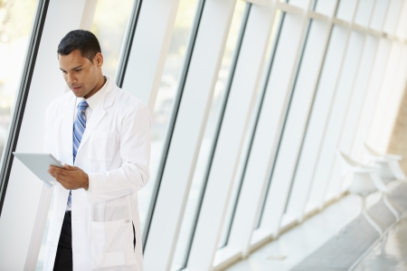 Doctor Using Digital Tablet In Corridor Of Modern Hospital photo