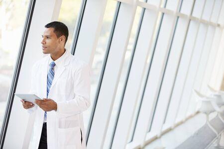 computer lab: Doctor Using Digital Tablet In Corridor Of Modern Hospital Stock Photo