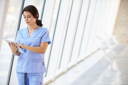 Nurse Using Digital Tablet In Corridor Of Modern Hospital photo