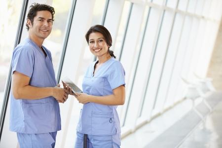 personal medico: Personal Médico Hablando En Pasillo Del Hospital Con Tableta digital Foto de archivo