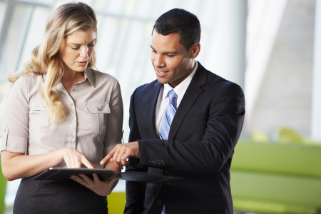 two people talking: Businessman And Businesswomen Having Informal Meeting In Office Stock Photo
