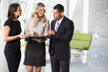 business woman standing: Businesspeople Having Informal Meeting In Modern Office