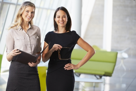 business relationship: Businesswomen Having Informal Meeting In Modern Office Stock Photo