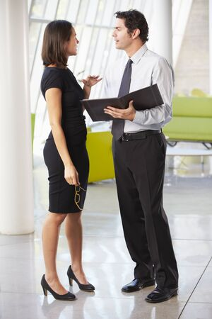two people talking: Businessman And Businesswomen Having Meeting In Office