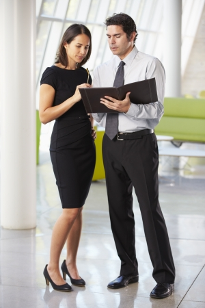 businessman standing: Businessman And Businesswomen Having Meeting In Office