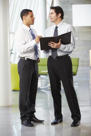 two people talking: Dos hombres de negocios La reuni�n informal en la oficina moderna