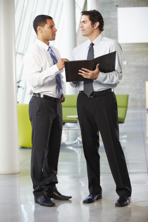 informal: Two Businessmen Having Informal Meeting In Modern Office