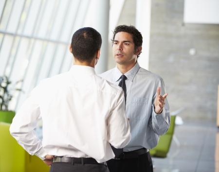 dos personas platicando: Dos hombres de negocios La reunión informal en la oficina moderna