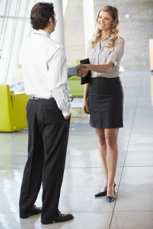 over the shoulder view: Businessman And Businesswoman Shaking Hands In Office