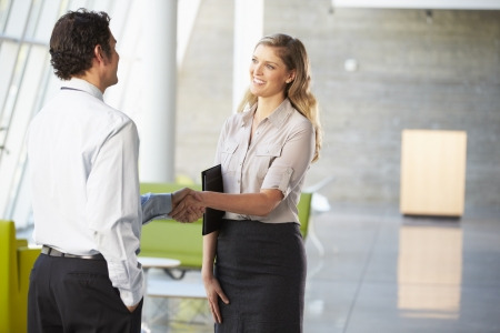 businesswoman standing: Businessman And Businesswoman Shaking Hands In Office
