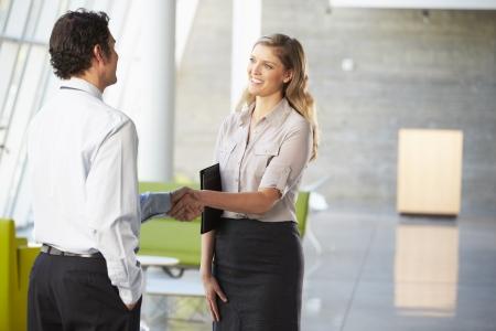 dandose la mano: Empresario y empresaria Shaking Hands In Oficina Foto de archivo