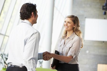 two people talking: Empresario y empresaria Shaking Hands In Oficina Foto de archivo