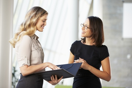 business relationship: Two Businesswomen Having Informal Meeting In Modern Office