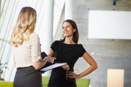 dos personas hablando: Dos Empresarias La reunión informal en la oficina moderna Foto de archivo