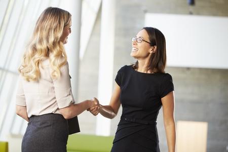 dandose la mano: Dos Empresarias Agitando Las Manos En La Oficina Moderna