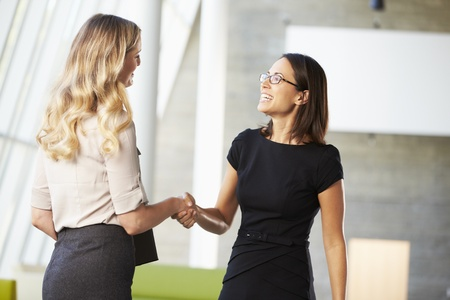 business relationship: Two Businesswomen Shaking Hands In Modern Office