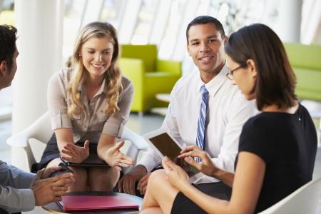 women talking: Businesspeople With Digital Tablet Having Meeting In Office