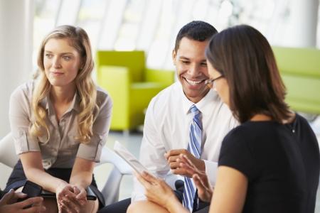 black business man: Avec les gens d'affaires R�union tablette num�rique Ayant Dans Office Banque d'images