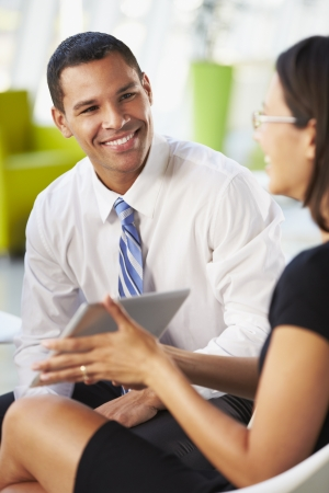 Businesspeople With Digital Tablet Having Meeting InOffice Stock Photo - 18736598