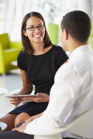 two people talking: Empresarios con la tableta digital que tiene InOffice Reuni�n