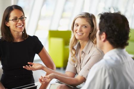 personas: Los empresarios tener la reuni�n alrededor de la mesa en la oficina moderna