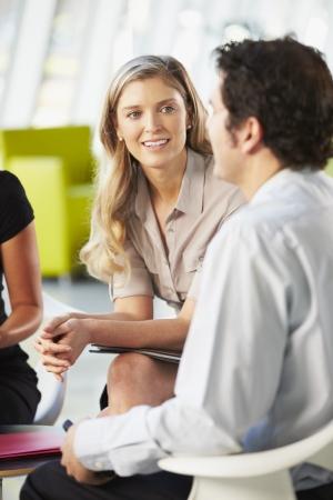 dos personas platicando: Los empresarios tener la reunión alrededor de la mesa en la oficina moderna