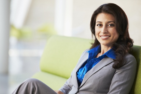woman on couch: Portrait Of Businesswoman Sitting On Sofa In Modern Office