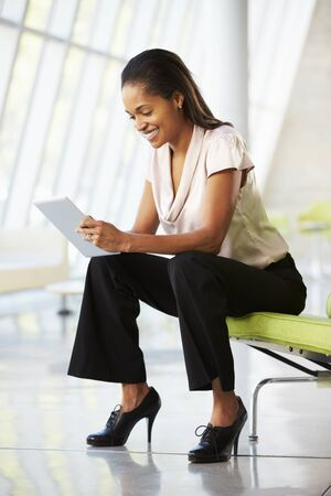 Businesswoman Sitting On Sofa In Office Using Digital Tablet Stock Photo - 18736787