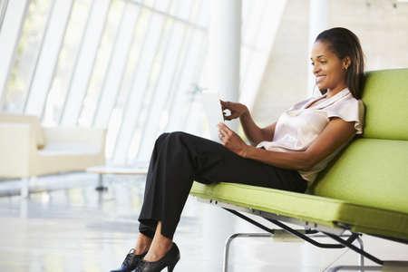 Businesswoman Sitting In Modern Office Using Digital Tablet photo