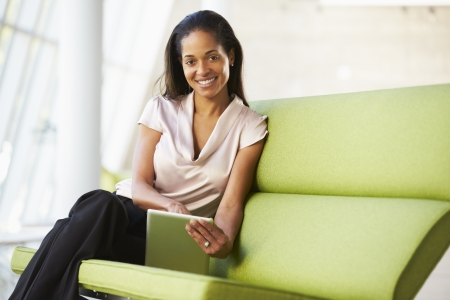 african american woman business: Businesswoman Sitting In Modern Office Using Digital Tablet